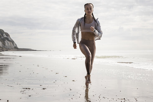 Front view of young female runner running barefoot along beach - CUF07156