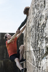 Young male free climber at top of sea wall helping friend climb up - CUF07159