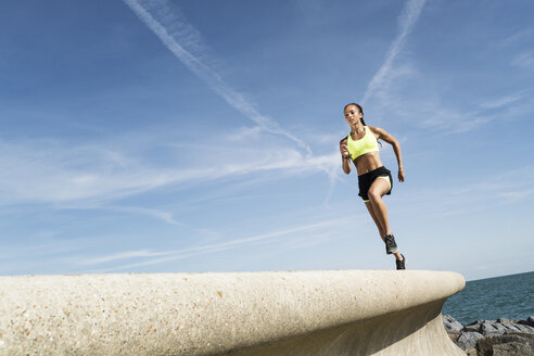 Low angle view of young female runner running along sea wall against blue sky - CUF07162