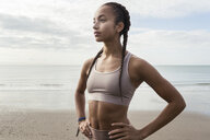 Young female runner with hands on her hips at beach - CUF07168