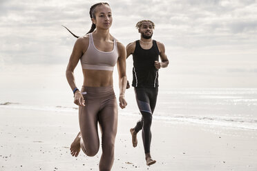Young male and female runners running barefoot along beach - CUF07174