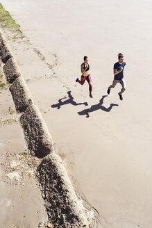 Young man and woman running along beach, elevated view - CUF07183