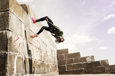 Young man, free running, outdoors, somersaulting from side of wall - CUF07186