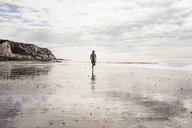 Young woman running along beach - CUF07195