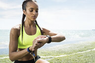 Young woman beside sea, wearing sports clothing, looking at activity tracker - CUF07204