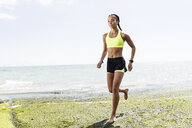 Young woman running, barefoot, beside sea - CUF07207