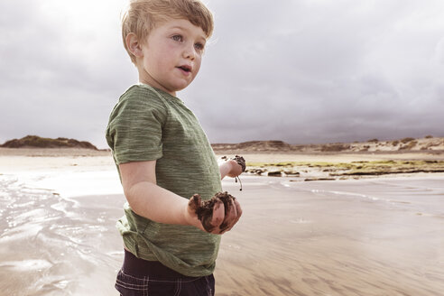 Young boy on beach, holding wet sand, Santa Cruz de Tenerife, Canary Islands, Spain, Europe - CUF07237