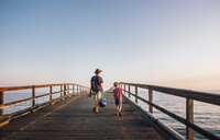 Rear view of father and son walking on pier, Goleta, California, United States, North America - CUF07243