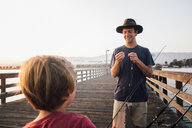 Father and son on pier preparing fishing rods, Goleta, California, United States, North America - CUF07246