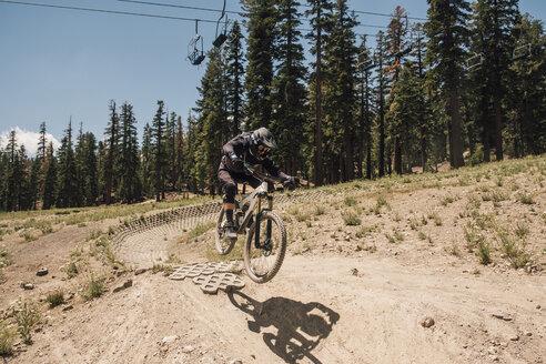 Man cycling on dirt track, jumping bike trick, Mammoth Lakes, California, USA, North America - CUF07252