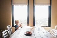 Boy sitting at dining table looking at camera, surprised, Fairfax, California, USA, North America - CUF07258