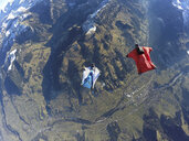 Aerial view of two wingsuit flyers, one on his back facing one in red suit flying above landscape - CUF07525