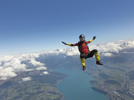 Female skydiver sitting up in free fall above clouds and lake - CUF07531