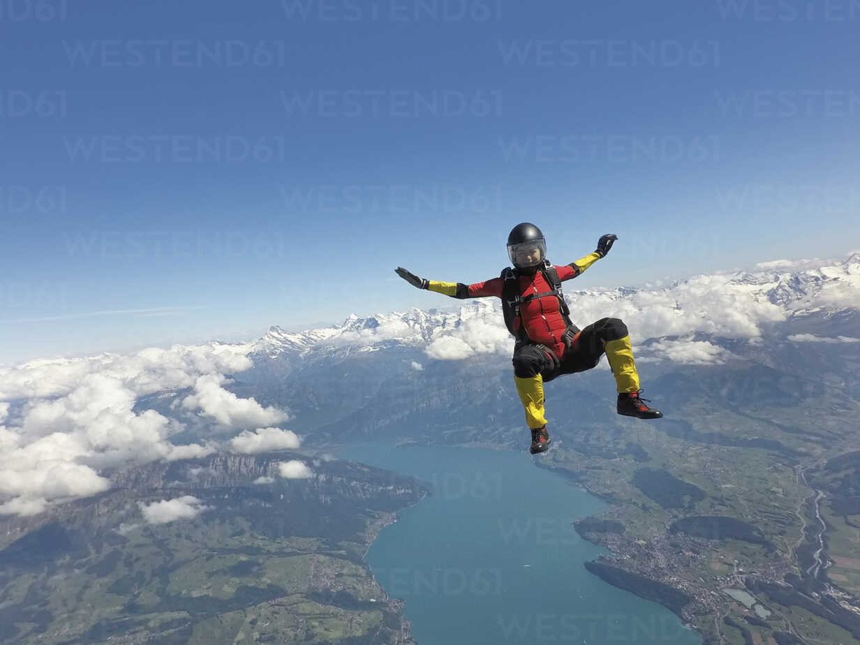 Female skydiver sitting up in free fall above clouds and lake - CUF07531 - Oliver Furrer/Westend61