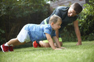 Father and son exercising in garden, doing push-ups - CUF07695