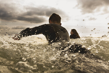 Two friends in sea, paddling on surfboards, rear view - ISF01510