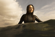 Young woman in sea, sitting on surfboard, paddling - ISF01513