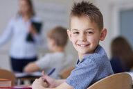 Portrait of smiling schoolboy in class - ABIF00374