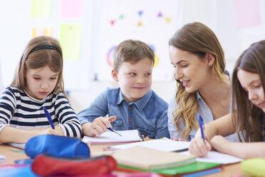 Teacher helping pupils with their tasks in class - ABIF00380