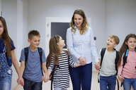 Smiling pupils and teacher walking hand in hand on corridor in school - ABIF00383