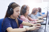 Pupils wearing headsets and using laptops in school - ABIF00386
