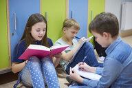Pupils learning together on corridor in school - ABIF00389