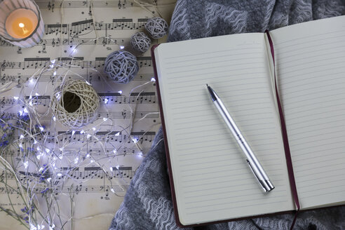 Pencil on notebook and fairy lights on music sheet - JUNF01054