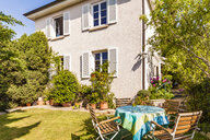 Germany, Stuttgart, one-family house, garden table with lawn chairs - WDF04658