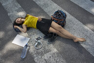 Young woman lying on zebra crossing taking a break - BEF00062
