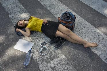 Young woman lying on zebra crossing taking a break - BEF00062