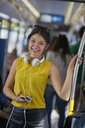 Portrait of smiling young woman with cell phone and headphones in underground train - BEF00068