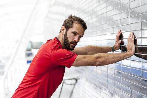 Man stetching at brick wall - DIGF04269