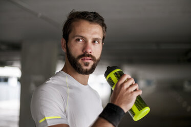 Athlete in parking garage holding drinking bottle - DIGF04281