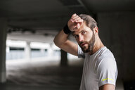 Portrait of athlete in parking garage with sweatband - DIGF04284