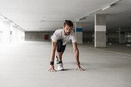 Athlete in starting position in parking garage - DIGF04290