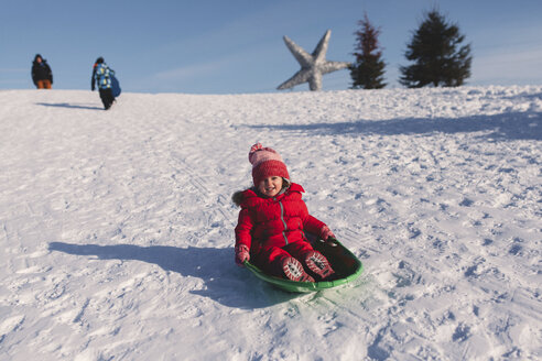 Girl in red knit hat tobogganing down snow covered hill - ISF01571