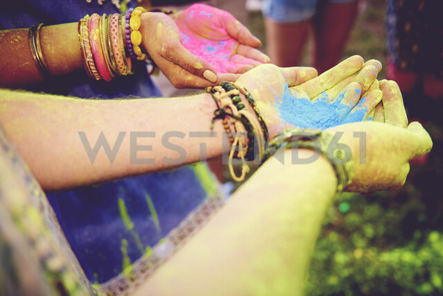 Pink and blue chalk cupped in young couples hands at festival - ISF01649 - Gpointstudio/Westend61