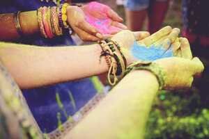Pink and blue chalk cupped in young couples hands at festival - ISF01649