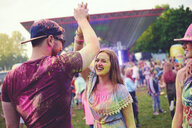 Young adults covered in coloured chalk powder high fiving at festival - ISF01655