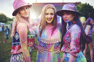Portrait of three young boho women covered in coloured chalk powder at festival - ISF01658