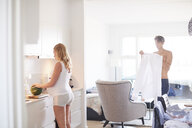 Pregnant young woman preparing breakfast while husband getting ready - CUF07740