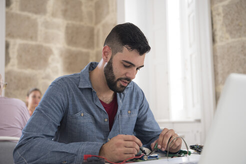 Young male computer technician repairing cable on office desk - CUF07794
