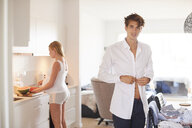 Portrait of man buttoning shirt and pregnant girlfriend in kitchen - CUF07797