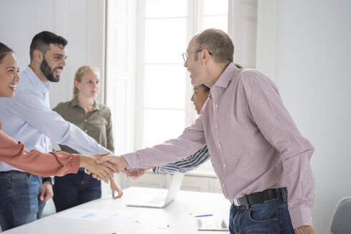 Businesswomen and men shaking hands at boardroom table - CUF07818