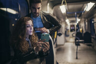 Couple using mobile phone in train, Florence, Italy - CUF07842
