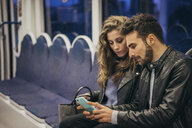 Couple using mobile phone in train, Florence, Italy - CUF07845