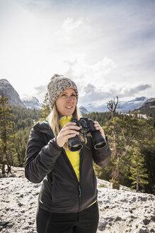 Woman holding binoculars, Yosemite National Park, California, USA - CUF07869
