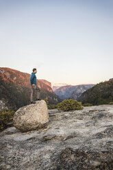 Man looking out from top of boulder, Yosemite National Park, California, USA - CUF07872