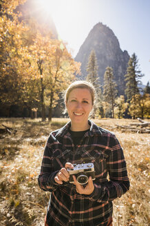 Portrait of woman holding camera in autumn landscape, Yosemite National Park, California, USA - CUF07875