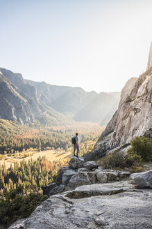 Man on boulder looking out at valley forest, Yosemite National Park, California, USA - CUF07878